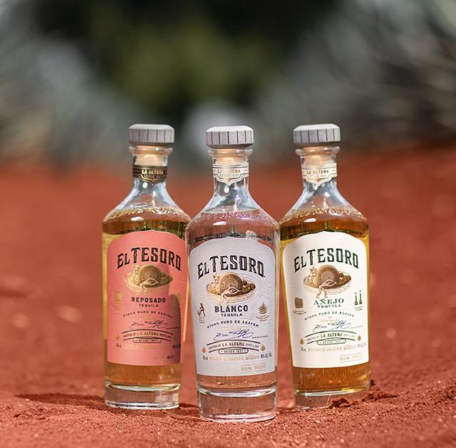 Three bottles of El Tesoro tequila side by side on the mineral-rich soil of the La Alteña distillery.
